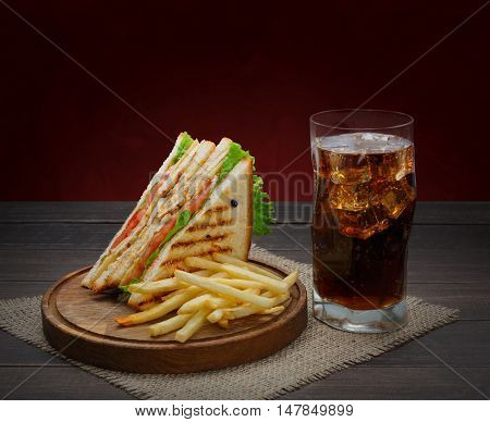Fast food meals at sandwich bar. Chicken and vegetables sandwich, potato chips and glass of cola drink with ice on wood. Take away composition. French fries with snack on wooden desk.