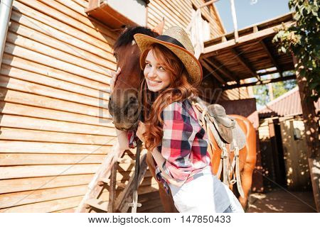 Cheerful pretty young woman cowgirl standing and hugging her horse on farm