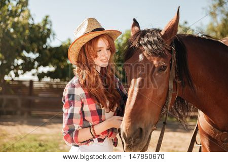 Cute lovely young woman cowgirl taking care of her horse on ranch