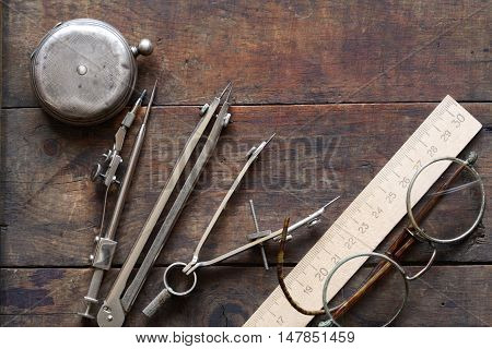 Set of vintage drawing instrument near ruler and spectacles