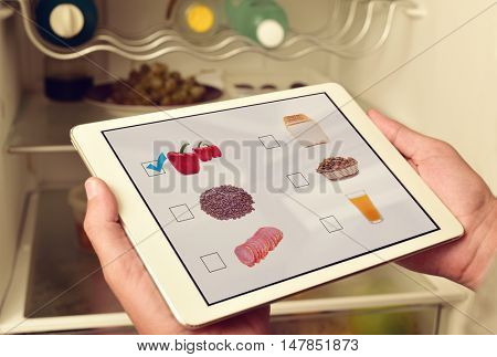 young man making his shopping list in his tablet computer, with pictures of different products shot by myself in its screen, in front of the fridge