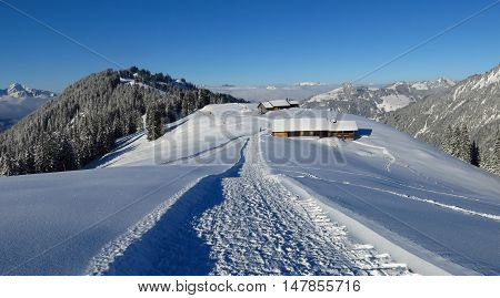 Winter hiking and sledging path on Mt Hohe Wispile Gstaad. Travel destination in the Swiss Alps.