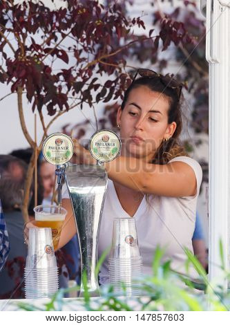 Seller Of Annual Beer Festival Pours Beer Into A Glass
