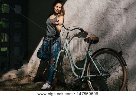 Beautiful yuong female in a torn denim standing with bicycle near the white wall