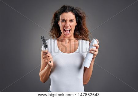 A beautiful young woman screaming while brushing her hair and holding a hairspray.