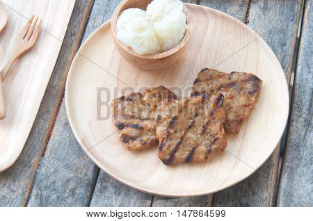 Grill pork with sticky rice on wood plate Thai food