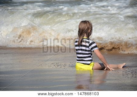 young girl sitting in sand and beach water