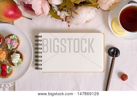 Mockup photography with flowers notebook and pen with nib. Desktop workplace designer artist painter top view. Modern trend template for advertising. Tea party invitation