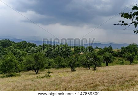 Landscape of field, orchard and mountain environs near by,  Giginski monastery, Breznik,  Pernik region, Bulgaria