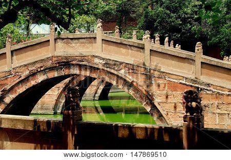 Deyang China - July 6 2007: Pink sandstone Pan Bridges span a lagoon at the 13th century Deyang Confucian Temple