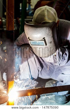 The worker with protective mask welding metal.