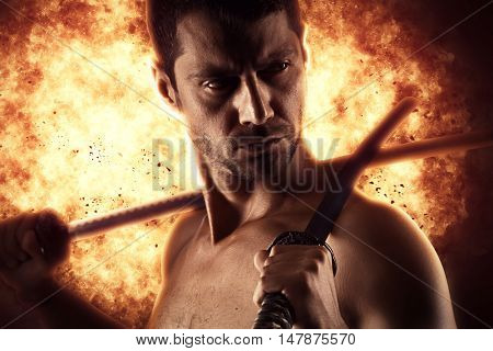 man with katana sword over explosion background
