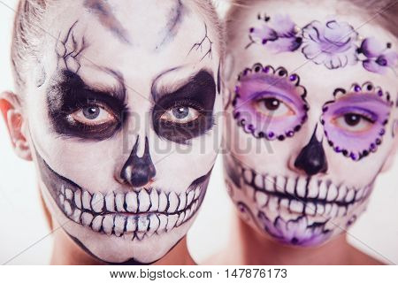 Two girls with Halloween face art on white background
