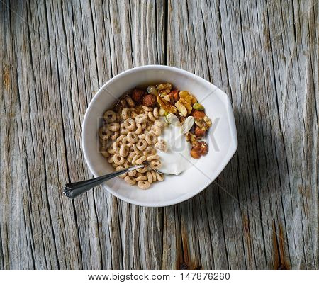 A Bowl of Wholegrain Cereal with Yogurt, Honey and Nuts/ Wood Background