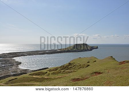 View to Worms Head or Penrhyn-gwyr on the Gower Peninsular at Rhossili in Wales United Kingdom. With people walking on beach at low tide