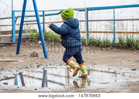 Toddler Boy Jumping In The Puddles