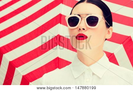 Fashion portrait of a beautiful girl with bright painted lips and sunglasses next to red striped background