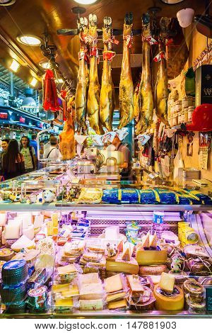 BARCELONA, SPAIN - AUGUST 25, 2016: Well known Boqueria Market in Barcelona. Jamon - spanish word for ham - traditional meat in spanish cuisine. Countertop with different food products made in Spain.