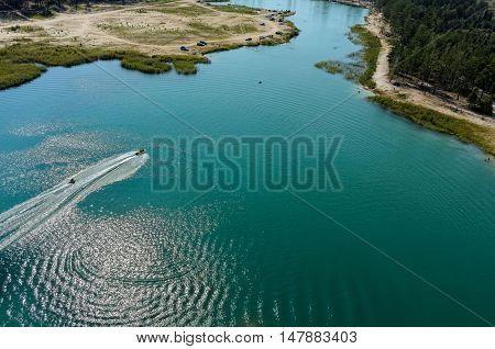 Aerial view onto beach on so-calles Blue Lake and hydrocycle tows the inflatable watercraft circle. Tyumen. Russia