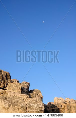 A waning moon over a rock outcropping on the summit of Mount Tai or Taishan located in Shandong province China.