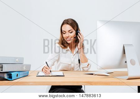 Smiling young woman making notes while talking with custumer on the phone at the call center over white background