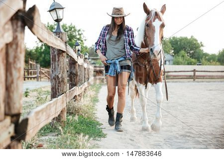 Attractive young woman cowgirl in hat smiling and walking with her horse in village
