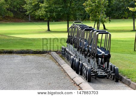 A golf trolleys waiting for golfers at golf course.