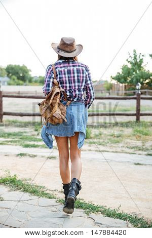 Back view of woman cowgirl in hat with backpack walking on ranch