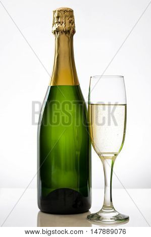 Champagne bottle with a glass cup on white background
