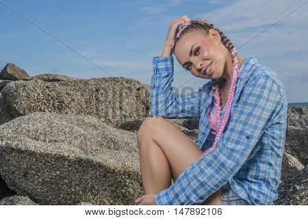 Young pretty girl with pink plaits wearing blue checked shirt smiling and looking into the camera while sitting on the rock during summer day over sky background