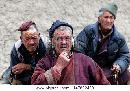 LAMAYURU, INDIA - JUNE 17, 2012: Men praying in Lamayuru Gompa during Yuru Kabgyat festival in Lamayuru Gompa.