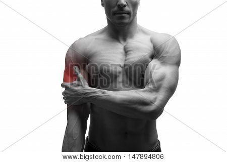 Man with pain in shoulder ache in muscular male body isolated on white background with red dot black and white photo