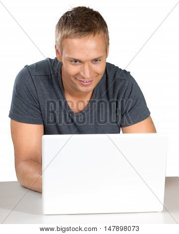 Smiling male sitting down and using a laptop