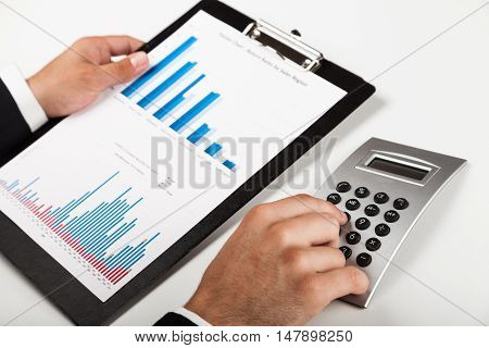 Close-up of a Businessman Analyzing Business Graphs with Calculator