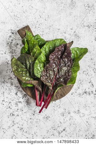 Fresh swiss chard or mangold on a wooden cutting board on a light background