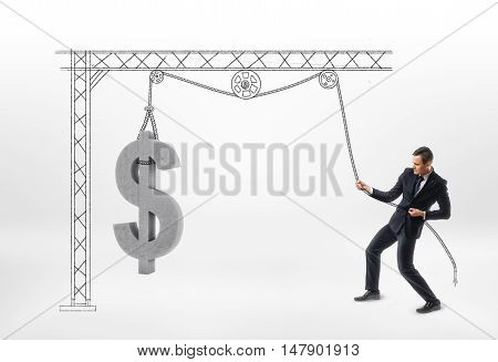 Businessman pulling big concrete 3d dollar sign with drawn pulley isolated on white background. Earning money. Making a profit. Advantage and benefit.