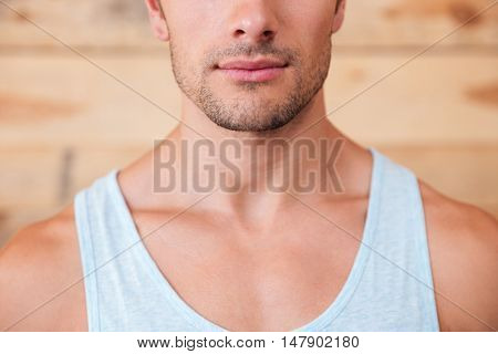 Closeup of serious confident young man over wooden background