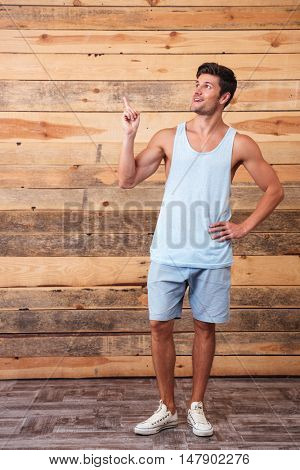 Full length of happy handsome young man syanding and pointing away over wooden background