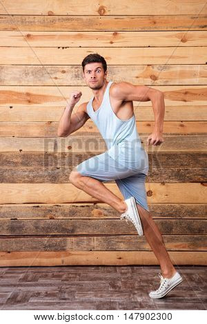 Full length of funny athletic young man running over wooden background