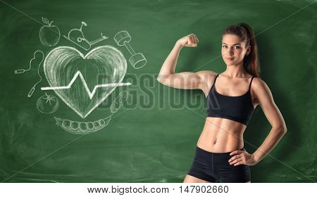 Cropped portrait of fitness girl showing her bicep on the background of a chalkboard with drawn beating heart and sport doodles. Cardio workoit. Athletic body.