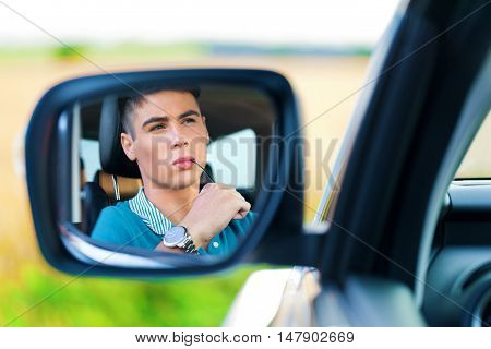 Portrait of Young Man Driving a Car in Side View Mirror