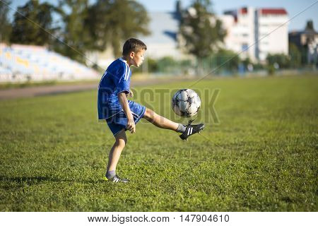 Boy kicking soccer ball on the football field at sunny day