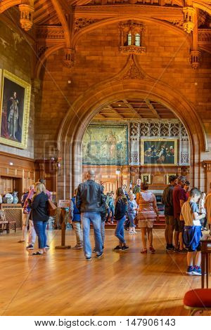 AUGUST 12, 2016--BAMBURGH, ENGLAND--Visitors to Bamburgh Castle in Bamburgh England look at the Great Hall of the castle and admire the beauty of the interior of the castle.
