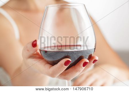 Woman drinking red wine from glass in home