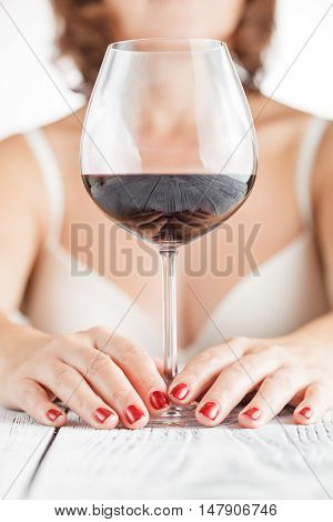 woman tasting wine from glass on bright background poster