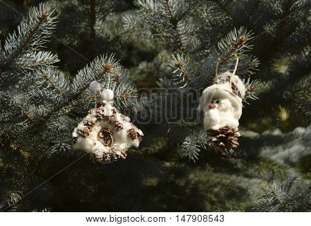 Christmas toys in the form of the gnome and the house. Toys are located on a fir-tree. The gnome and the house are made of fir cones and cotton wool