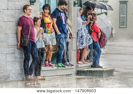 Quebec City, Canada - July 27, 2014: A group of people hide from heavy rain under a building while three walk with umbrellas.