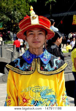 Jie Zi Ancient Town China - October 1 2010: Chinese youth wearing vintage ceremonial robe and hat in Wastepaper Pagoda Square