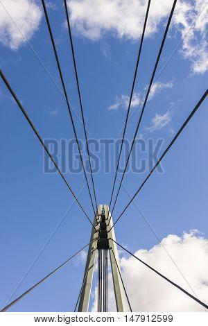 Iron ropes of suspension bridge blue sky in background