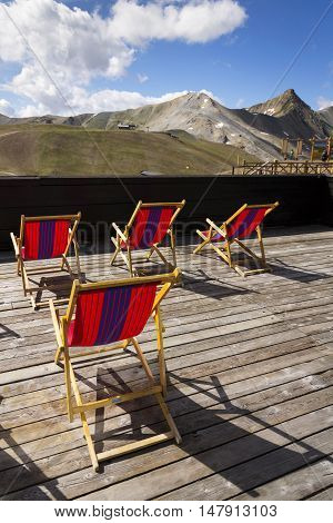 Colorful Empy Deckchairs On Terrace With Italian Alps Mountains View